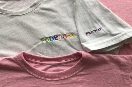 """Tres camisetas dobladas y bordadas con las palabras """"La MODA es un acto POLITICO"""", """"PODEROSA"""" y """"orgullosamente feminista"""""""
