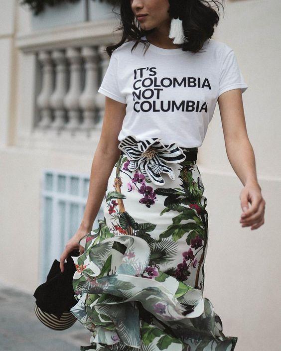 """Modelo con una camiseta blanca con las palabras """"It's Colombia Not Columbia"""" en letras negras y una falda de boleros con un patrón floral."""